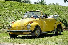 Stock Photo: Yellow Volkswagen Beetle Convertible parked on the grass.