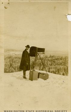 Washington State Historical Society - One of our featured Click! exhibit photographer, Asahel Curtis, stands next to his camera equipment on a snowy ridge in Mount Rainier National Park, undated ca. 1915-1920.