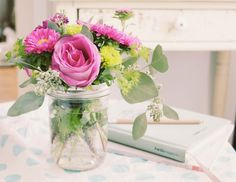 Arrange flowers in mason jars on a dining table