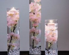 This table decoration will include: 1 - 20 x 4 Cylinder Vase 1 - 14 x 4 Cylinder Vase 1 - 12 x 4 Cylinder Vase Cherry Blossom Silk Floral Strands (not real silk) or white - choose from the drop down 3 - Floating candles 1 - Acrylic crystals ca Yellow Centerpieces, Wedding Table Centerpieces, Wedding Flower Arrangements, Flower Centerpieces, Wedding Decorations, Table Decorations, Centerpiece Ideas, Flowers Vase, Quinceanera Centerpieces
