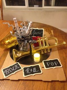 musical centerpiece-scrolled music sheets, plastic instruments, candles wrapped in music, and chalkboard music genres.