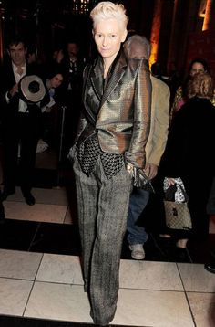 Tilda Swinton chose Haider Ackermann's jacquard print blazer, dual print shirt, and wide leg tweed palazzo pants to attend the private viewing of the 'David Bowie Is' exhibition in London. [Photo Credit: Dave M. Benett/Getty Images] )