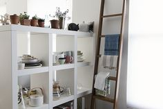 Casual way of organizing and displaying tableware and kitchen utensils. Love the little potted plants on the top shelf.