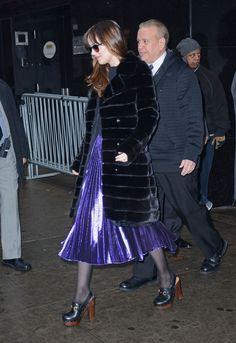 Dakota Johnson wears a purple pleated skirt, a J. Mendel fur jacket, Gucci clogs, and sunglasses