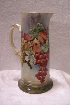 Refined Porcelain Limoges Tankard Pitcher featuring a 'Harvest of Multi-colored Grapes- Green, Gold, Purple(Black), and Red'  and accompanied foliage against a blushed hue background is carried out perfectly  The twisted handle is decorated with gold scrolls adding a taste if elegance to the piece. Entirely handpainted.
