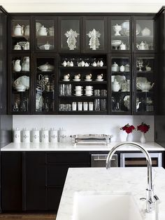 Black glass-front cabinetry + white counters and backsplash