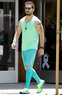 Shia LaBeouf clearly digs neon! Just look at the hunky dude, in classic wayfarer shades, sporting a vibrant sea-foam green tank, and aqua shorts and socks!