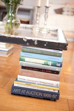 diy cheap coffee table. books as legs & old frame or window as table top.