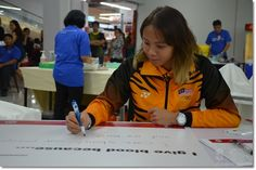 Pandelela Rinong Pamg writing a message on a poster for the blood donation campaign.