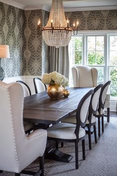 black salvaged wood dining table, Restoration Hardware Salvaged Wood Trestle Rectangular Extension Dining Table,  lined with black and white French round back dining chairs and wingback captain chairs placed at each end of the table atop a diamond print rug.
