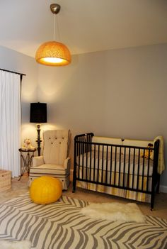 Sophisticated nursery.  The lighting, chair and rug really spice it up.  Would, however, up something on the blank wall!