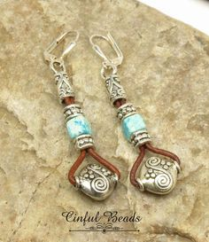 These leather dangle earrings consist of Tibetan style beads and turquoise ceramic beads hanging on 1.5mm natural red brown leather cord. Tibetan style cord ends top off the earrings that dangle from silver plated leverback earwires. The earrings measure 2 1/2 long from the top