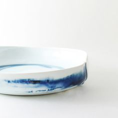 "porcelain dish. approx 11"" wide, 2"" high. wheel thrown, then hand-altered. glazed glassy clear with blue abstract marks.food/microwave safe. please handwash.our products are made in the wabi sabi tradition. crazing, irregular textures and marks are part of the handmade nature of the work, and should be embraced."