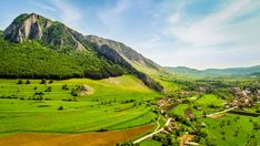 Aerial view of Rimetea, Transylvania, Romania. Grass meadow with wild flowers and the limestone rock Piatra Secuiului dominating the countryside. Limestone Rock, Transylvania Romania, Gaudi, Aerial View, Wild Flowers, Countryside, Golf Courses, Mountains, Travel