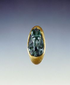 Minerva (Getty Museum). A bust of the goddess Athena carved in high relief has been set into the bezel of this hollow gold ring. Athena wears a snake-edged aegis and a helmet in her role as warrior goddess. Roman, A.D. 1- 100. Chalcedony and gold