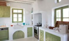 peasant style room, with light pastel green, rustic kitchen cabinets, and matching window panes, white lime plaster walls