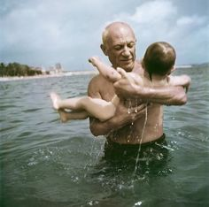 [Pablo Picasso playing in the water with his son Claude, Vallauris, France], 1948. © Robert Capa
