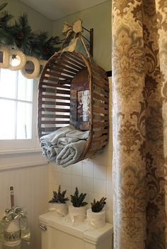 Wall mounted vintage basket with ribbon used as towel storage- great idea for a small bathroom! @ Home Improvement Ideas