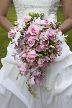 Roses and Orchids Bouquet. Make a dramatic entrance with a grand bouquet! This bride wanted to make a big impact and chose roses and orchids in beautiful pale pinks and purples to help her out.    Event and flowers by : MJ Weddings & Events
