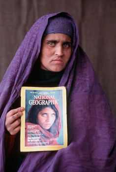 Picture of Sharbat Gula holding a 1985 National Geographic magazine