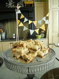 Yummy Carmel Oatmeal bars piled high on a cake stand w/ a banner hanging above.