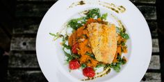 Healthy recipe: sweet mashed potatoes with arugula, oven roasted cherry tomatoes, garlic and pesto, with a fish schnitzel on the side.