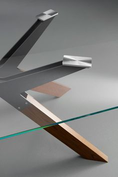 Steel, a table with four legs structure made of laser cut bended sheet metal and solid wood. The top is available in different materials and finishes.