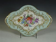 <b>A 19th century French porcelain cabaret tray</b></i></u> <br /> <br /> of lobed shape with twin handles, the well floral painted on a light blue ground with gilt highlights, red and blue painted marks <br /> 41cm wide