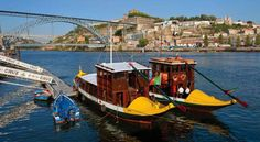 "RABELOS: In Porto, on the banks of Douro, traditional boats called ""rabelos"" await passengers."