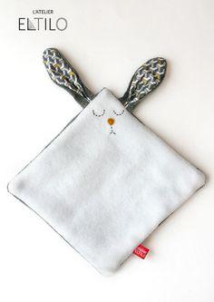 Lapin tout doux est cousu à la main. Son pelage est fait d'un côté à poil court gris ultra doux et de l'autre de la flanelle blanche.  Ses oreilles sont en coton à motifs.  - 20023131