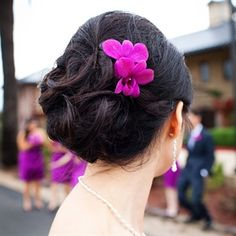Phing accented her soft, curled updo with a single radiant orchid.