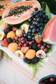 Create an easy but eye-pleasing spread by piling fresh fruit onto a cake platter. Slice larger fruits like watermelon and papaya in half to anchor the smaller fruit.