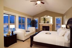 Large windows on the left wall have shorter furniture, including a side table…