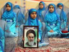 A young Iranian girl holds a portrait of the founder of Iran's Islamic Republic, Ayatollah Ruhollah Khomeini during a ceremony marking the 36th anniversary of his return from exile at Khomeini's mausoleum in a suburb of Tehran. Khomeini returned from exile in 1979, the trigger for a revolution which spawned an Islamic state now engulfed in a deep political crisis ATTA KENARE/AFP/Getty Images 1 February 2015