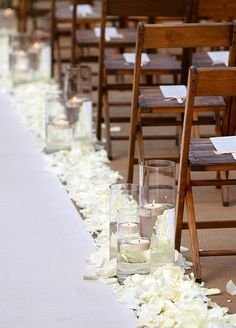 The aisle is lined in white rose petals and hurricane glasses that filled with floating candles.
