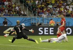United States' Matt Besler tries to defend as Belgium's Daniel Van Buyten takes a shot on goalkeeper Tim Howard during the World Cup round of 16 soccer match between Belgium and the USA at the Arena Fonte Nova in Salvador, Brazil, Tuesday, July 1, 2014. (AP Photo/Natacha Pisarenko)