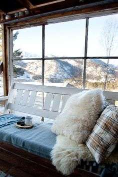 Fluffy fur & plaid pillows - Window seat - Picture window - Snowy mountain view