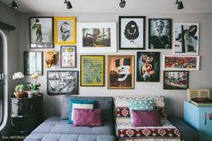 parede de quadros e sofá cinza neutro