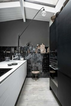 Swing-arm Lamps in a stunning black kitchen