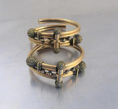 Stunning circa late 1800s rare matched pair of rose gold filled ornate antique Etruscan Wedding Bangle Bracelets.  Each bangle has a spring hinged front with a center bar and two round ball shaped ends with ornate granulation. Bead like accents along the center of the bracelets with matching Etruscan round shaped end caps on opposite ends.  When closed the bracelets measures 1 7/8 across. When hinge is open, bracelet will accommodate a size 6 inch wrist comfortably. My wrist measures 6 1...