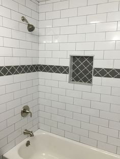 Large white subway tile with dark gray grout and gray fleur accent tile in Master Bath Shower at our Long Beach House!