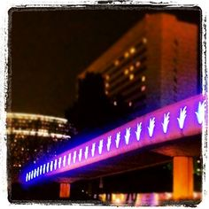Unity Bridge glowing at night.  The pedestrian bridge crosses Bristol Street and connects South Coast Plaza with The Westin, Segerstrom Center for the Arts and South Coast Repertory.