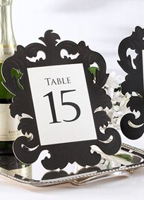 This classic black openwork baroque-inspired table number cards give clear direction to your guests while taking the wow impact of your table decor to another level.  Features and facts:   Heavyweight-artboard self-standing table card with baroque design.  Self-propping folding frame stand on back.  Card measures 10 h x 7 3/4 w x 2 1/2 d (when standing).  Sold in a set of numbers 1 through 15.  Some easy assembly required.View Alternate Link