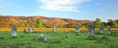 Lochbuie Stone Circle · Isle of Mull · This is a small and well preserved stone circle overlooked by spectacular Ben Buie and standing within the grounds of Lochbuie House. The circle was originally nine granite stones, set in a ring about 12 metres in diameter, with the tallest stone being about two metres high. It is mainly composed of granite slabs which have been positioned with their flatter faces towards the inside of the circle. One of the original stones has been removed and replaced…