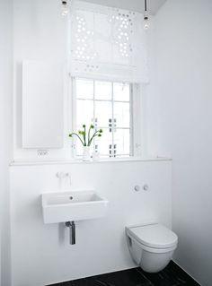 Badeværelset er blevet forkælet med vask og toilet designet af Philippe Starck. Gardinerne er, ligesom i resten af lejligheden, lavet af svensk kamuflagenet købt på surplusandadventure.com