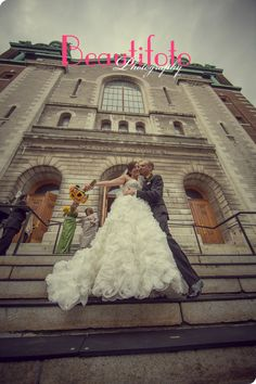 the bride and groom kissing in front of their church: Saint-Zotique paroiss