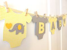 **Cute and adorable banner for baby showers!!**  This banner is a perfect touch for both gender neutral baby showers!  Light Yellow plaid patterned and solid Gray one-piece bodysuits are made of high quality heavy cardstock paper and strung on ivory satin ribbon using mini wooden clothespins. Alternating light yellow and gray WELCOME BABY letters and the center elephant design are mounted with pop-dots, adding that special something with a 3D look! - Each bodysuit measures about 6.5 in width…