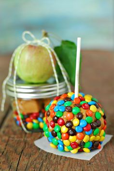 Caramel Apple In A Jar  8 oz wide mouth mason jar 12 wrapped caramels 1/4 cup mini M&M's Small apple Lollipop stick 1 tsp water