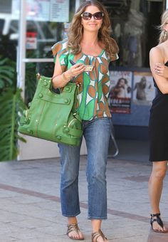 Steal The Look / Strapped in Strap details add visual appeal to this green leather bag.