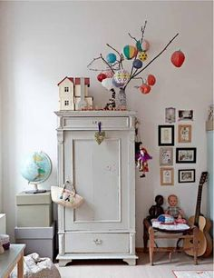 paper lanterns hanging from twigs in simple and organized kids room.... use an armoire... small gallery
